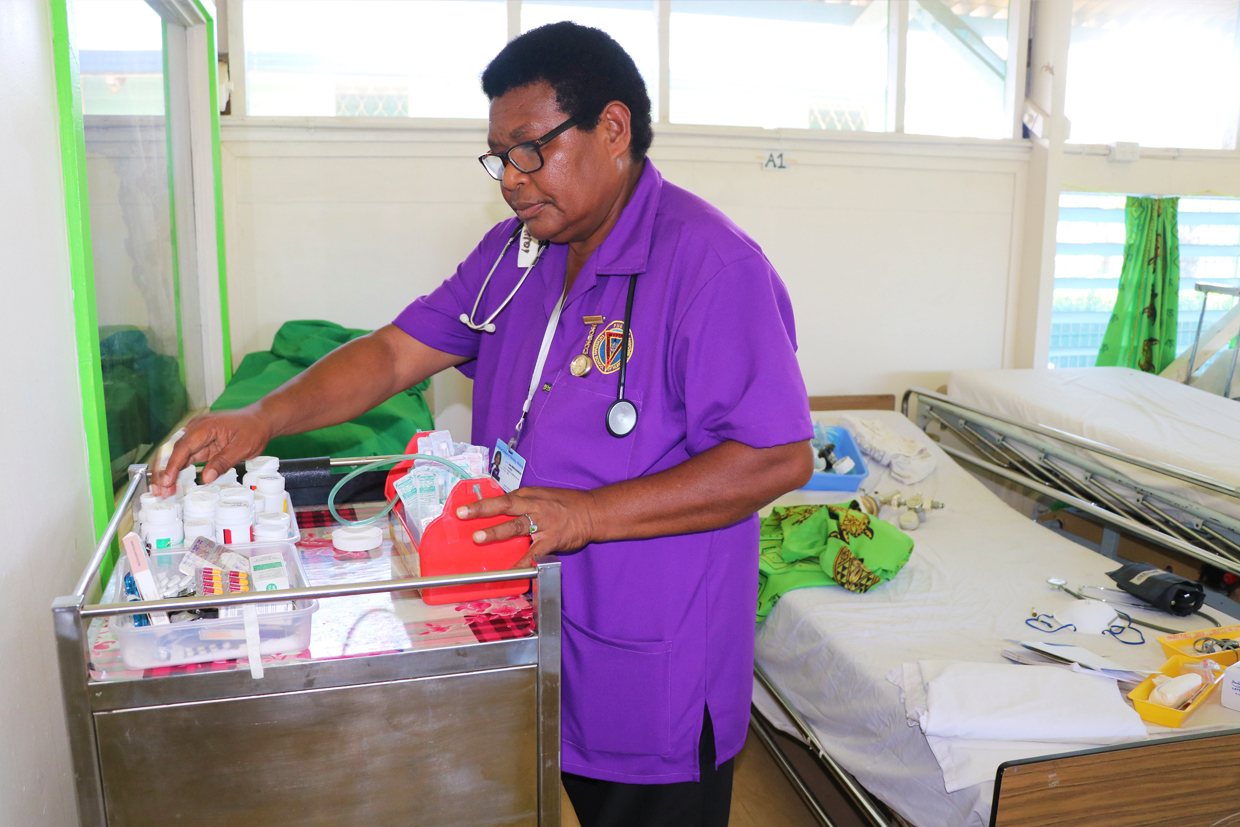The image depicts a midwife working in a hospital ward